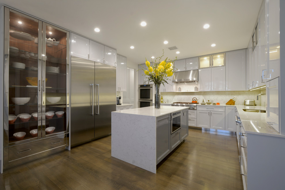 Ejemplo de cocinas en L contemporánea con fregadero de un seno, armarios estilo shaker, puertas de armario blancas, salpicadero blanco, electrodomésticos de acero inoxidable, suelo de madera en tonos medios y una isla