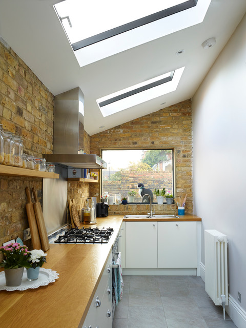 Example of a trendy l-shaped kitchen design in London with a drop-in sink, flat-panel cabinets, white cabinets, wood countertops, brick backsplash and no island