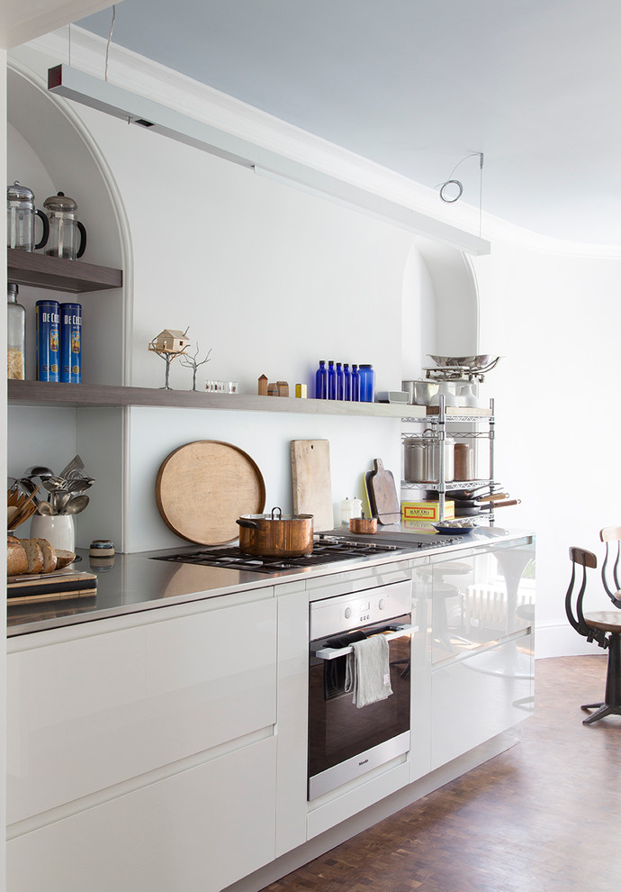Medium sized contemporary galley kitchen/diner in London with glass-front cabinets, grey cabinets, stainless steel worktops, integrated appliances and no island.