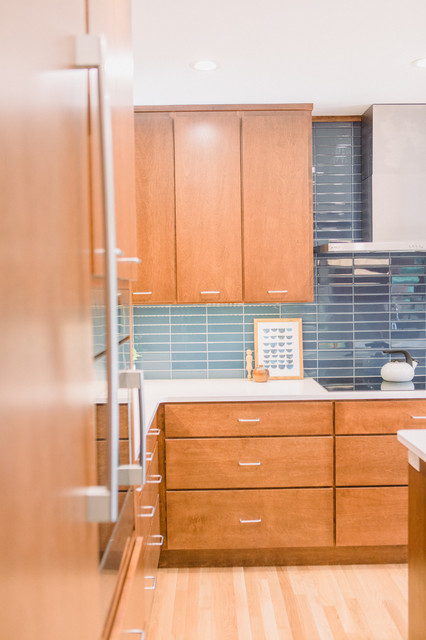 Mid-sized 1950s l-shaped light wood floor and brown floor open concept kitchen photo in Grand Rapids with an undermount sink, flat-panel cabinets, medium tone wood cabinets, quartz countertops, blue backsplash, ceramic backsplash, paneled appliances, an island and white countertops