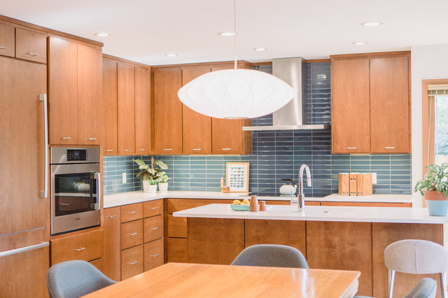 Inspiration for a mid-sized 1950s l-shaped light wood floor and brown floor open concept kitchen remodel in Grand Rapids with an undermount sink, flat-panel cabinets, medium tone wood cabinets, quartz countertops, blue backsplash, ceramic backsplash, paneled appliances, an island and white countertops