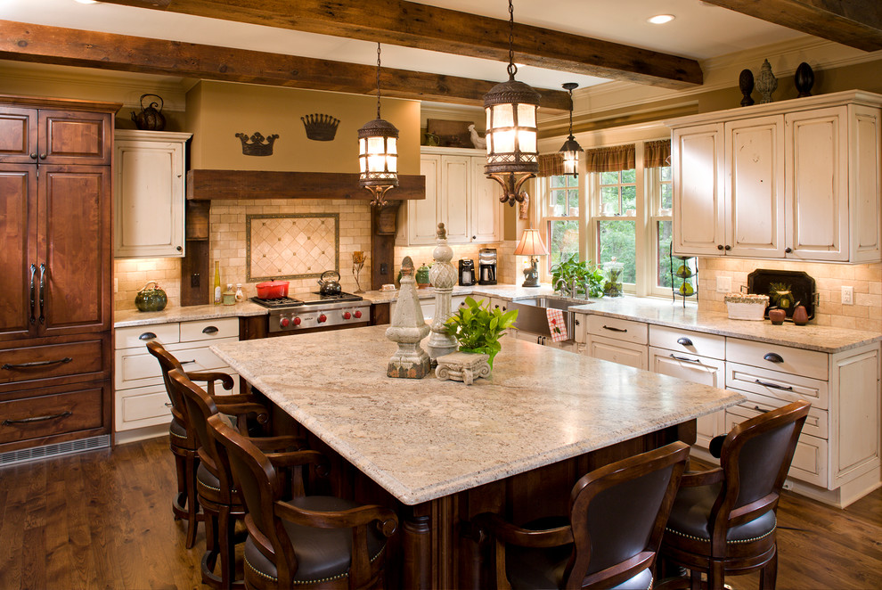 Example of a large classic l-shaped medium tone wood floor open concept kitchen design in Minneapolis with a farmhouse sink, beige cabinets, raised-panel cabinets, an island, granite countertops, beige backsplash, paneled appliances and limestone backsplash