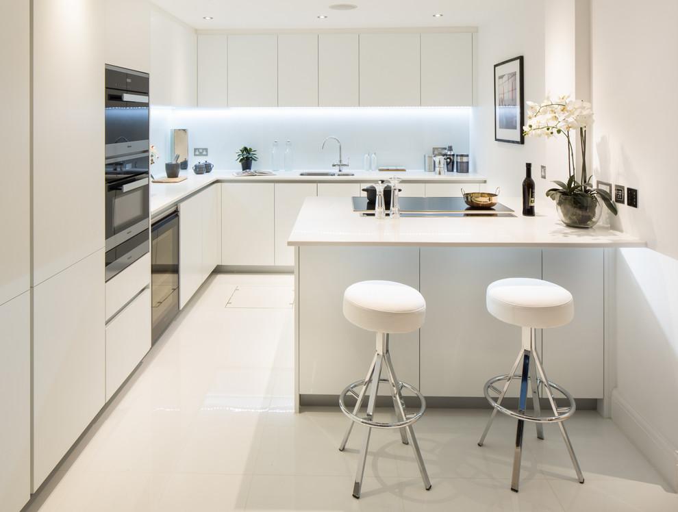 Modelo de cocinas en L actual con fregadero bajoencimera, armarios con paneles lisos, puertas de armario blancas, salpicadero azul, electrodomésticos de acero inoxidable y una isla
