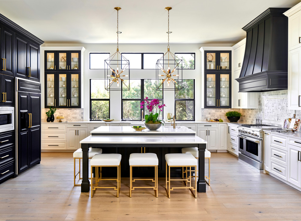 Example of a transitional u-shaped light wood floor and beige floor kitchen design in Austin with a farmhouse sink, raised-panel cabinets, black cabinets, gray backsplash, paneled appliances, an island, white countertops and quartz countertops