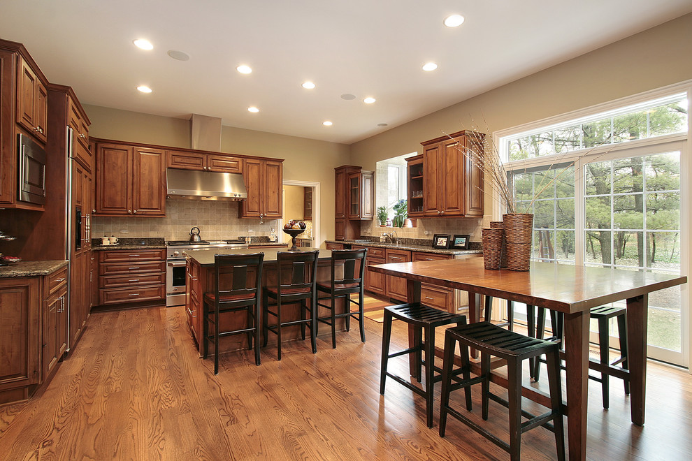 Eat-in kitchen - traditional u-shaped eat-in kitchen idea in Chicago with raised-panel cabinets, medium tone wood cabinets, beige backsplash and paneled appliances
