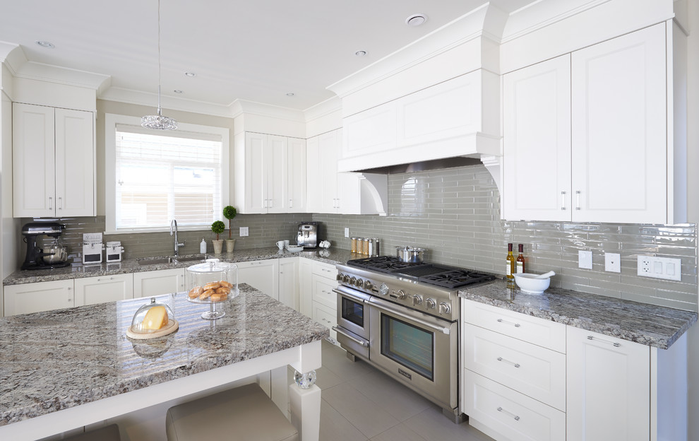 Open concept kitchen - mid-sized transitional l-shaped porcelain tile open concept kitchen idea in Vancouver with an undermount sink, shaker cabinets, white cabinets, granite countertops, gray backsplash, glass tile backsplash, stainless steel appliances and an island