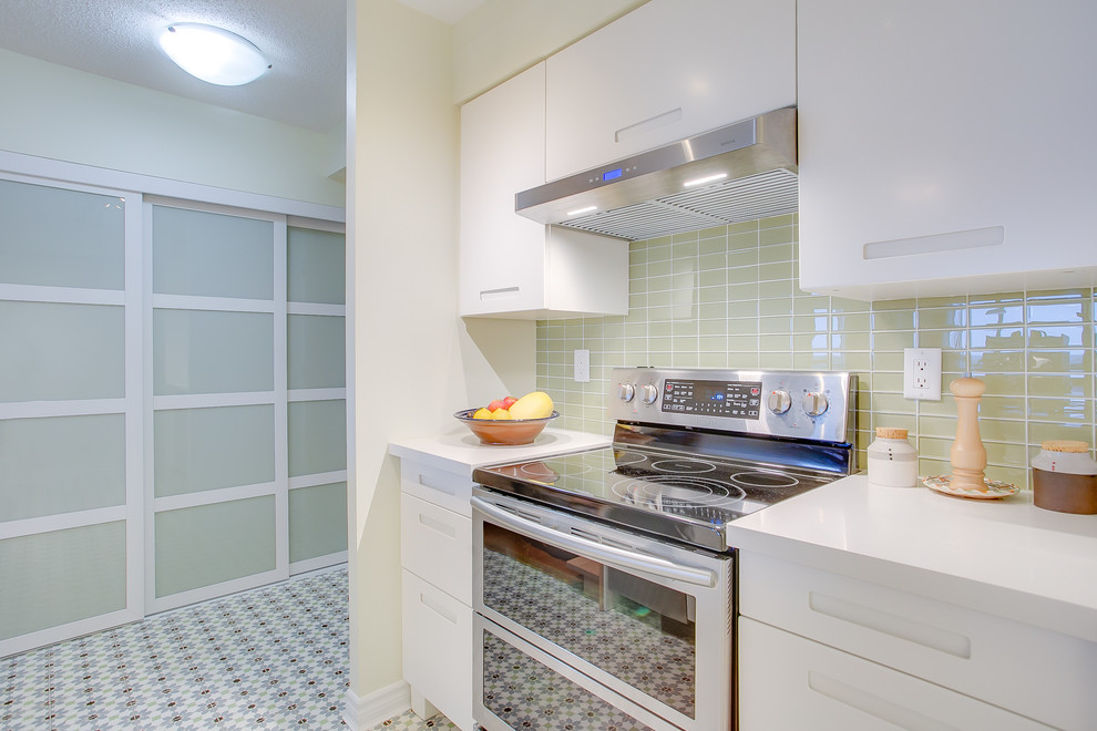 Kitchen pantry - small contemporary galley cement tile floor and multicolored floor kitchen pantry idea in Toronto with an undermount sink, flat-panel cabinets, white cabinets, quartzite countertops, green backsplash, a peninsula, glass tile backsplash, stainless steel appliances and white countertops