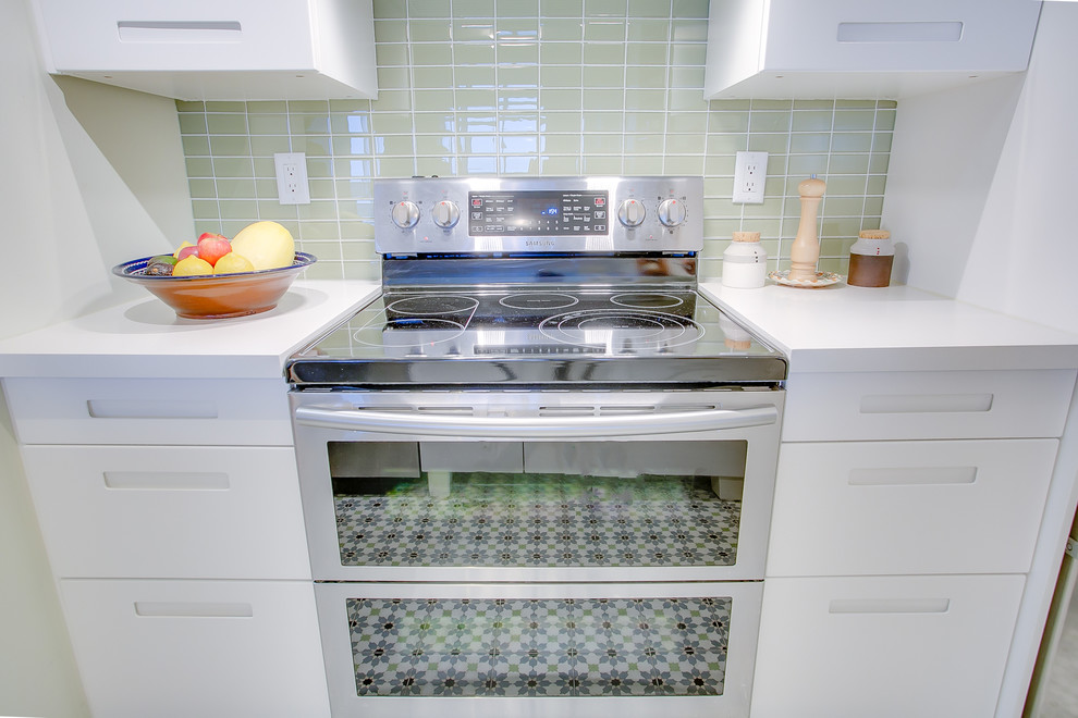 Example of a small trendy galley cement tile floor and multicolored floor eat-in kitchen design in Toronto with an undermount sink, flat-panel cabinets, white cabinets, quartzite countertops, green backsplash, glass tile backsplash, stainless steel appliances, a peninsula and white countertops