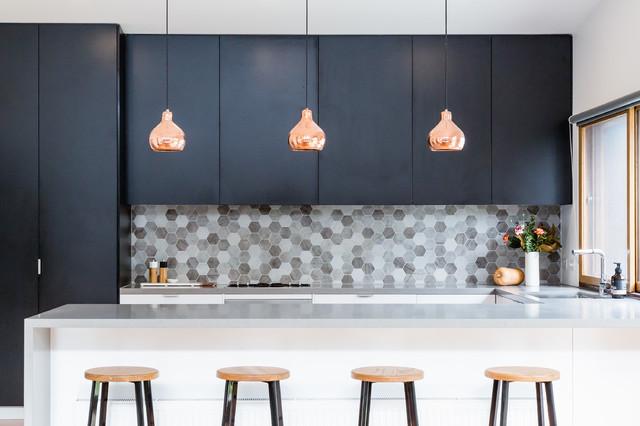 Exemple d'une cuisine tendance en U avec un évier encastré, un placard à porte plane, des portes de placard noires, une crédence grise, une crédence en mosaïque et une péninsule.