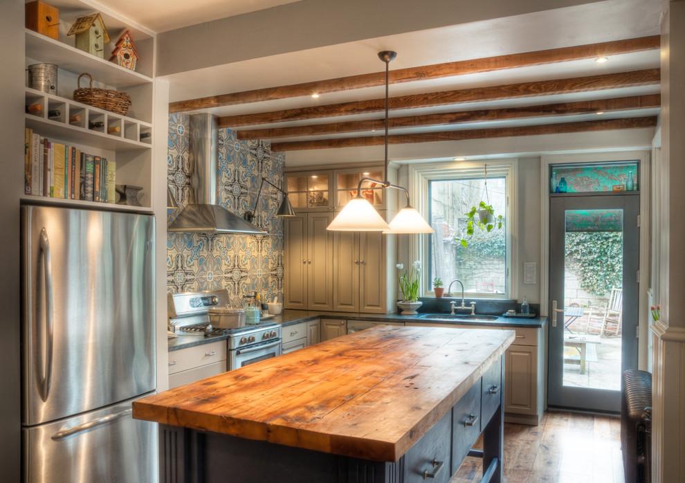 Foto de cocinas en L tradicional con armarios con paneles con relieve, encimera de madera, puertas de armario azules, salpicadero azul, electrodomésticos de acero inoxidable y de obra