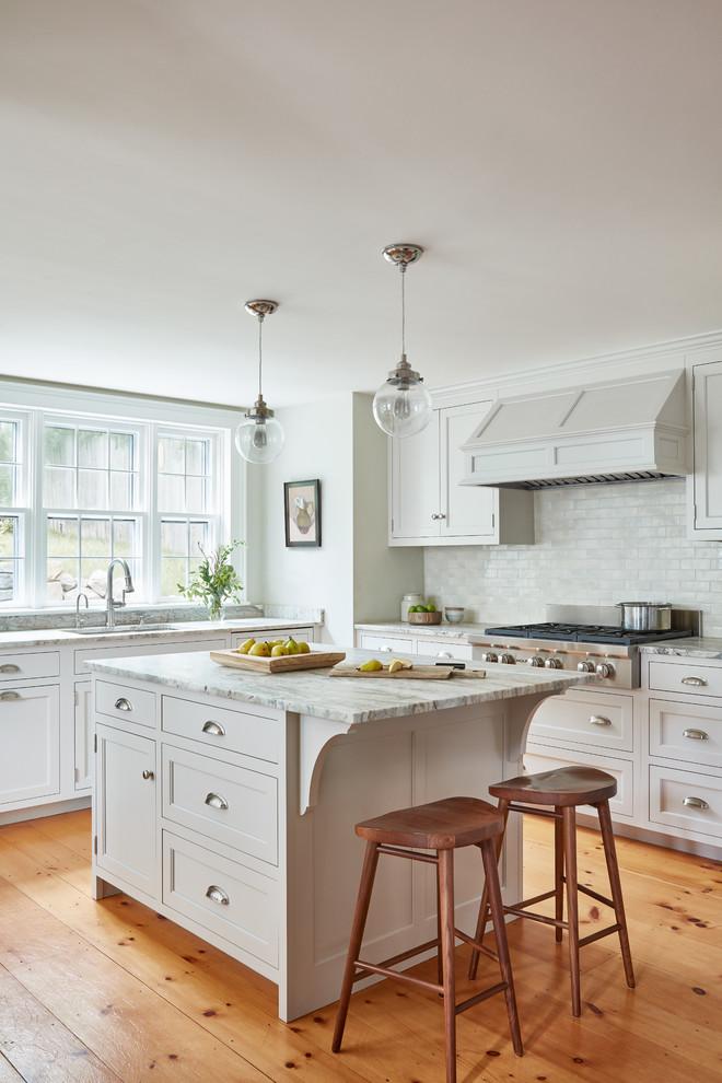 Modelo de cocinas en L tradicional con fregadero bajoencimera, armarios estilo shaker, puertas de armario blancas, salpicadero blanco, suelo de madera en tonos medios, una isla y suelo marrón