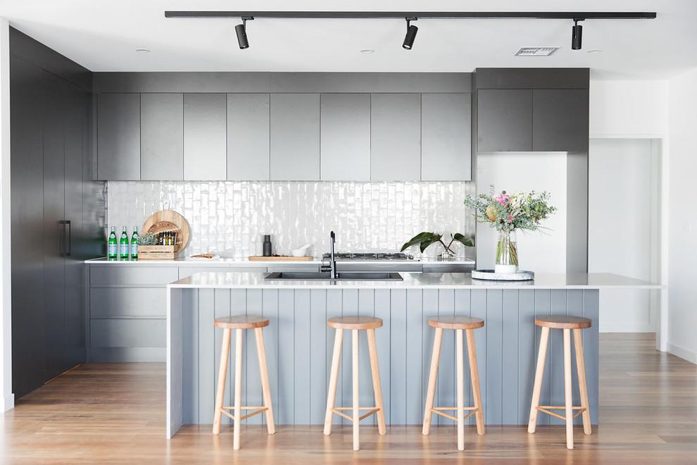 Immagine di una cucina minimalista di medie dimensioni con lavello a doppia vasca, ante nere, top in quarzo composito, paraspruzzi grigio, paraspruzzi con piastrelle diamantate, elettrodomestici neri, pavimento in legno massello medio, isola e pavimento marrone