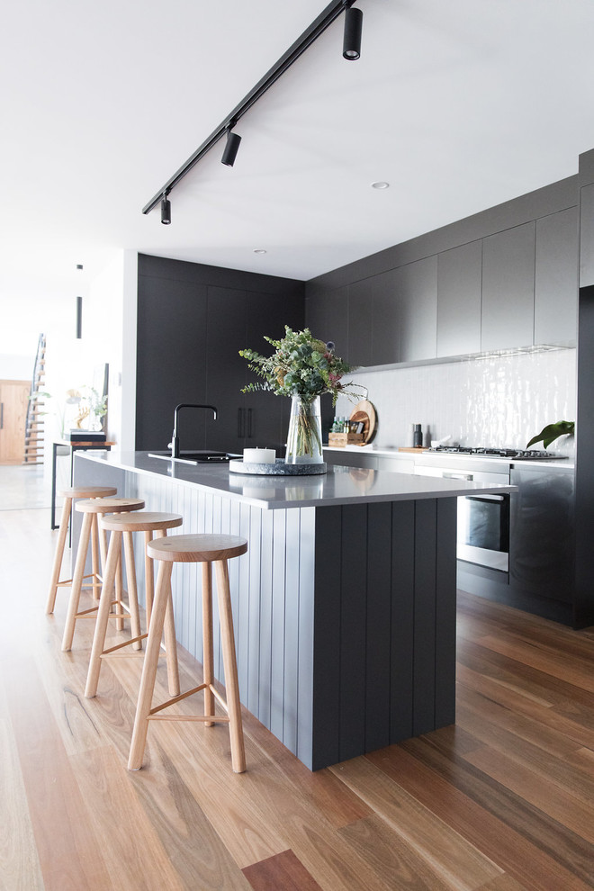This is an example of a medium sized contemporary l-shaped open plan kitchen in Canberra - Queanbeyan with a double-bowl sink, black cabinets, engineered stone countertops, medium hardwood flooring, an island, brown floors, flat-panel cabinets and white splashback.