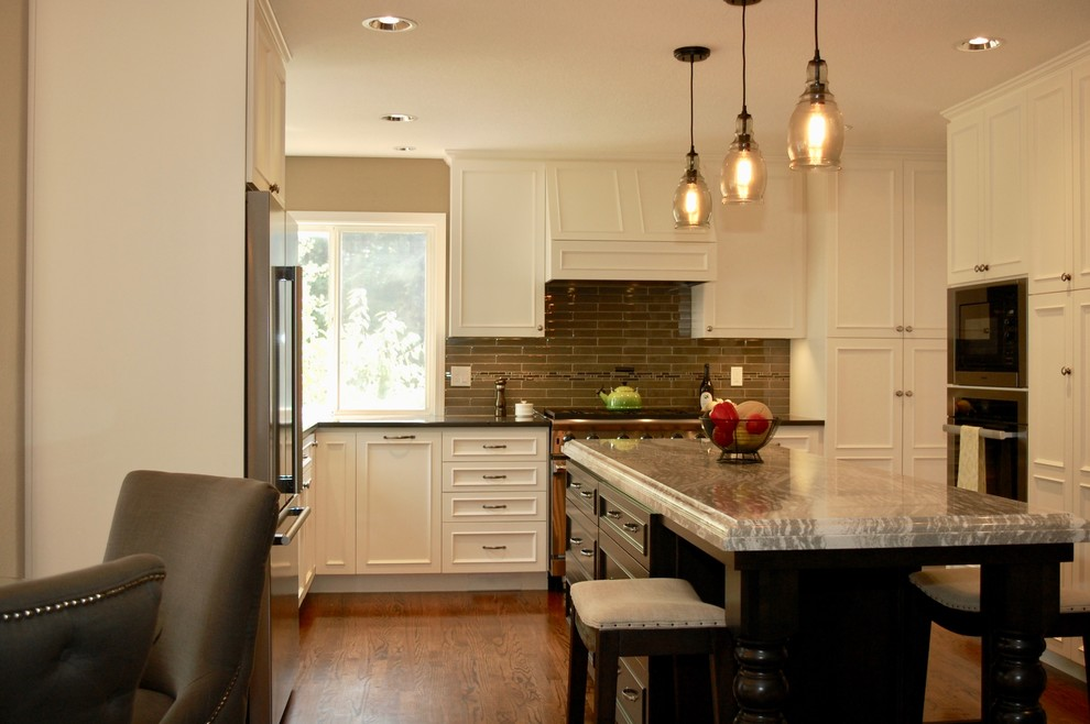 Inspiration for a large timeless u-shaped medium tone wood floor open concept kitchen remodel in Portland with an undermount sink, beaded inset cabinets, white cabinets, quartz countertops, beige backsplash, glass tile backsplash, stainless steel appliances, an island and black countertops