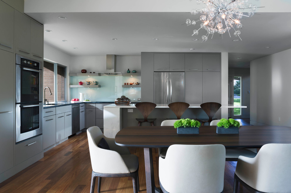 Inspiration for a large modern l-shaped medium tone wood floor eat-in kitchen remodel in Austin with flat-panel cabinets, gray cabinets, marble countertops, glass sheet backsplash, stainless steel appliances, an undermount sink and an island