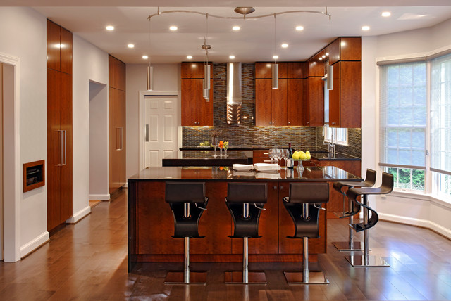 Example of a large trendy u-shaped light wood floor eat-in kitchen design in DC Metro with flat-panel cabinets, medium tone wood cabinets, multicolored backsplash, paneled appliances, granite countertops, glass tile backsplash, two islands and an undermount sink