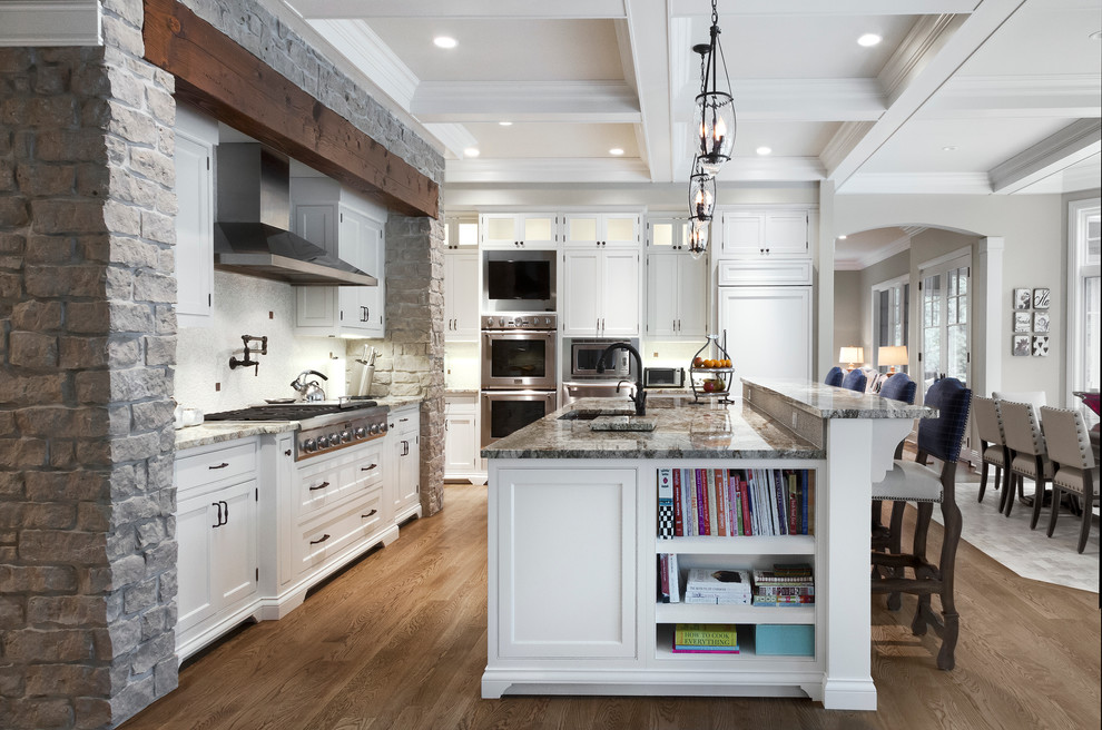 Example of a classic eat-in kitchen design in Chicago with an undermount sink, beaded inset cabinets, white cabinets, granite countertops, white backsplash and stainless steel appliances