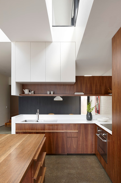 Design ideas for a mid-sized contemporary l-shaped kitchen in Melbourne with an undermount sink, flat-panel cabinets, stainless steel appliances, travertine floors, an island and dark wood cabinets.