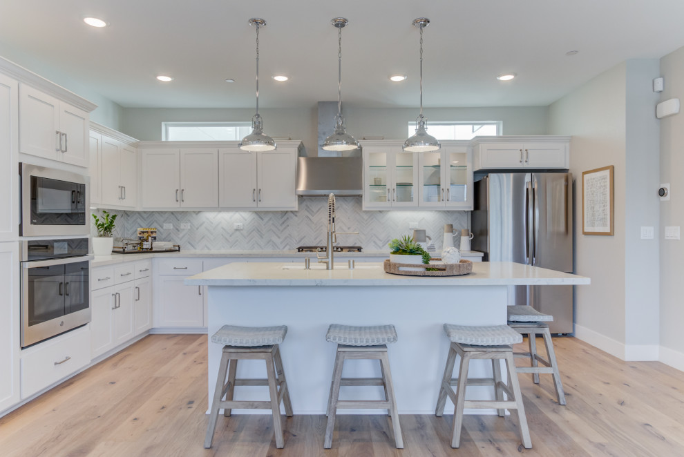 Transitional l-shaped light wood floor and beige floor open concept kitchen photo in San Francisco with an undermount sink, white cabinets, stainless steel appliances, an island, shaker cabinets, gray backsplash and white countertops