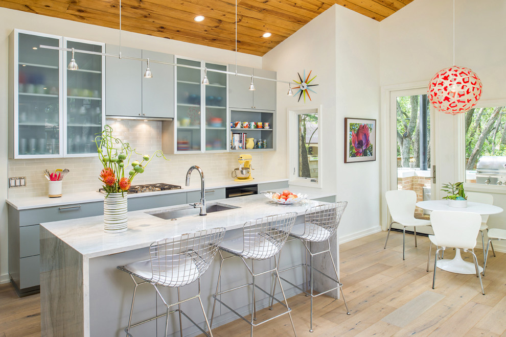 1960s galley light wood floor open concept kitchen photo in Austin with an undermount sink, flat-panel cabinets, gray cabinets, quartzite countertops, gray backsplash, ceramic backsplash, stainless steel appliances and an island