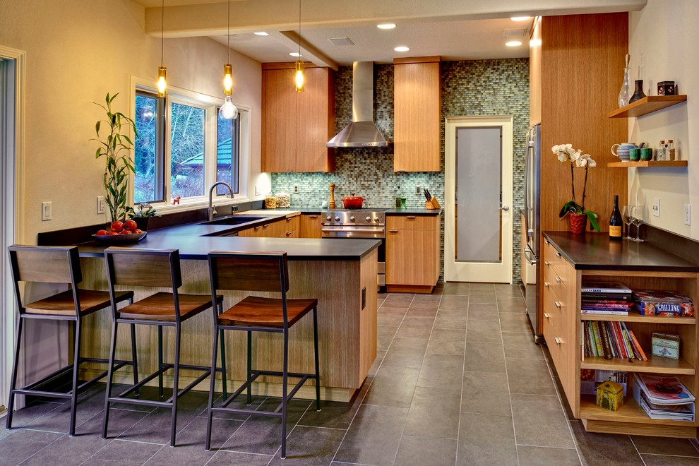 Minimalist u-shaped kitchen photo in Portland with flat-panel cabinets, medium tone wood cabinets, green backsplash and stainless steel appliances