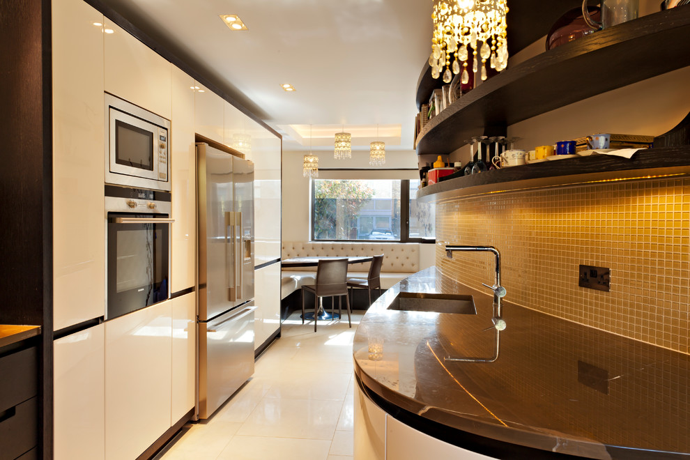 Example of a trendy galley ceramic tile eat-in kitchen design in London with an undermount sink, flat-panel cabinets, white cabinets, yellow backsplash, glass tile backsplash, stainless steel appliances and no island