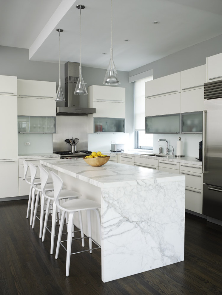 Inspiration for a contemporary l-shaped kitchen remodel in New York with stainless steel appliances, glass-front cabinets, white cabinets and marble countertops