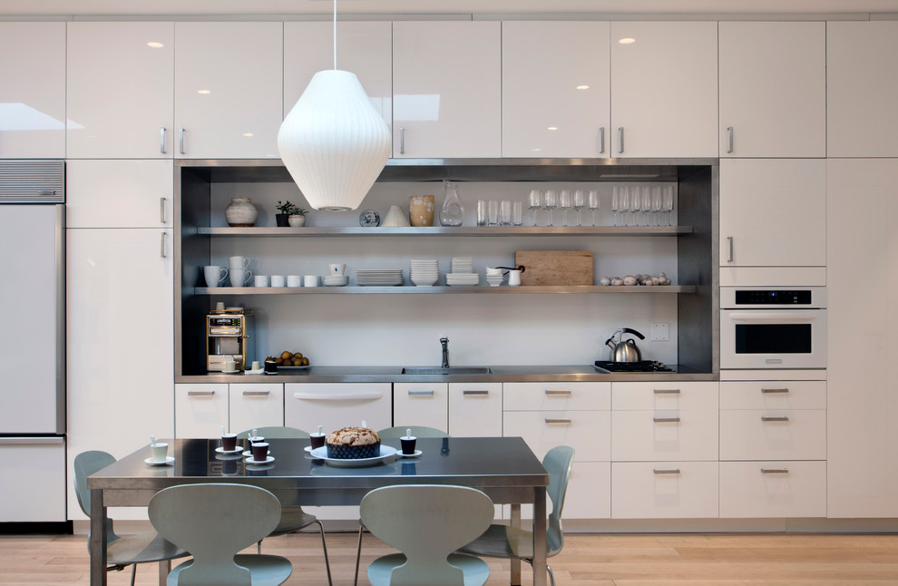 Trendy single-wall eat-in kitchen photo in New York with white appliances, flat-panel cabinets, stainless steel countertops, white cabinets and an integrated sink
