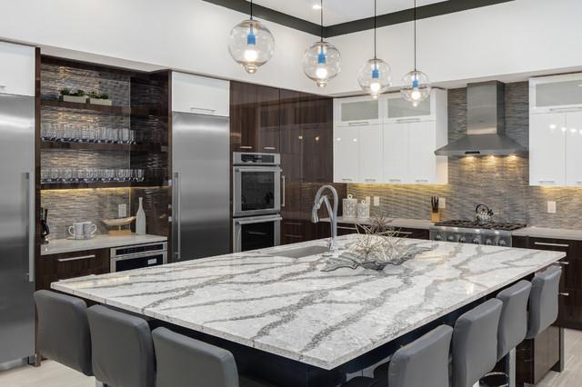 Large minimalist u-shaped porcelain floor open concept kitchen photo in Orlando with stainless steel appliances, an island, a drop-in sink, flat-panel cabinets, dark wood cabinets, quartz countertops, metallic backsplash and glass tile backsplash