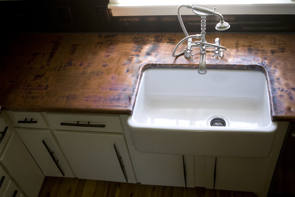 Elegant kitchen photo in Charlotte with a farmhouse sink and copper countertops