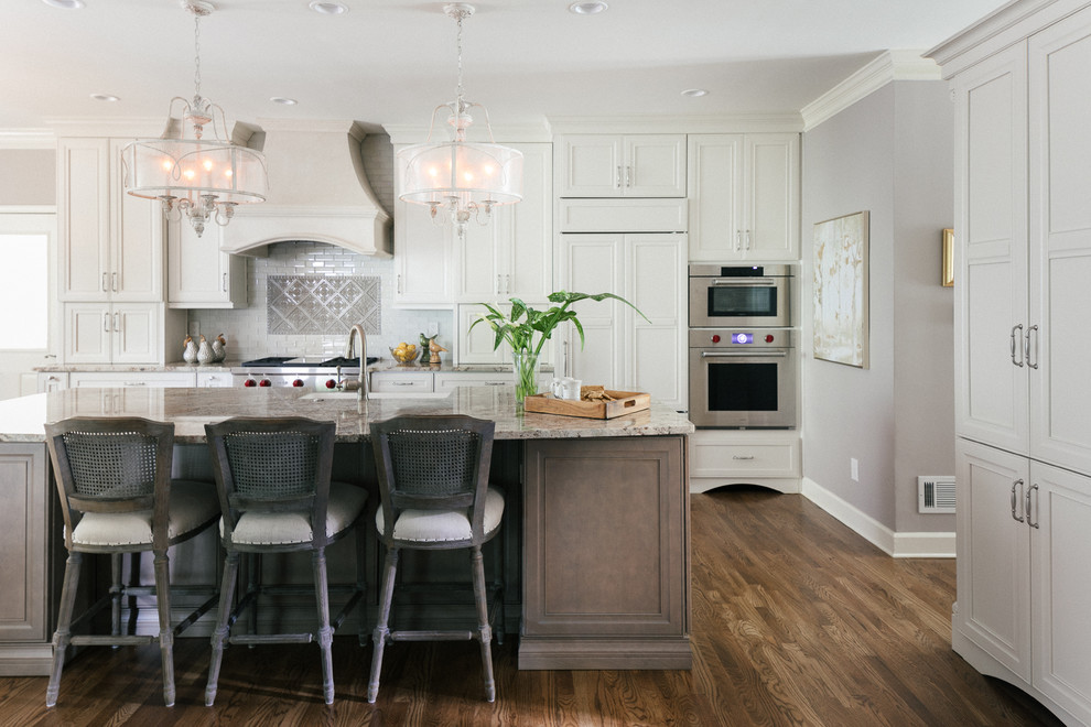 Example of a large classic l-shaped brown floor and medium tone wood floor open concept kitchen design in Atlanta with a farmhouse sink, stainless steel appliances, an island, flat-panel cabinets, gray cabinets, granite countertops, multicolored backsplash, glass tile backsplash and beige countertops