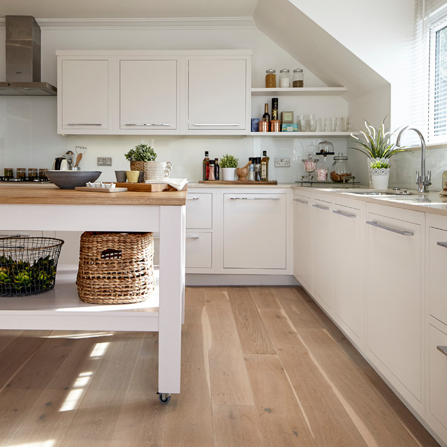 Example of a country l-shaped light wood floor kitchen design in London with an undermount sink, flat-panel cabinets, white cabinets, wood countertops, stainless steel appliances and an island