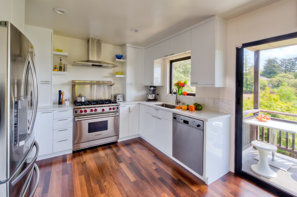 Small trendy u-shaped medium tone wood floor and beige floor kitchen photo in San Francisco with stainless steel appliances, an undermount sink, flat-panel cabinets, white cabinets, marble countertops, white backsplash, subway tile backsplash and no island