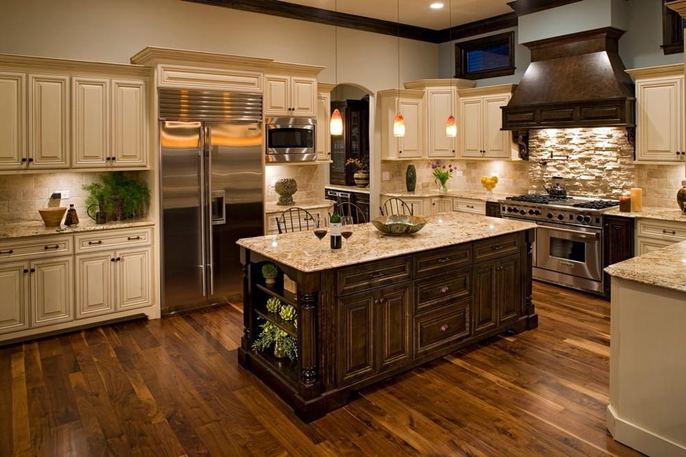 Inspiration for a mid-sized timeless u-shaped dark wood floor enclosed kitchen remodel in Chicago with raised-panel cabinets, beige cabinets, beige backsplash, stone tile backsplash, stainless steel appliances, granite countertops, an island and a double-bowl sink
