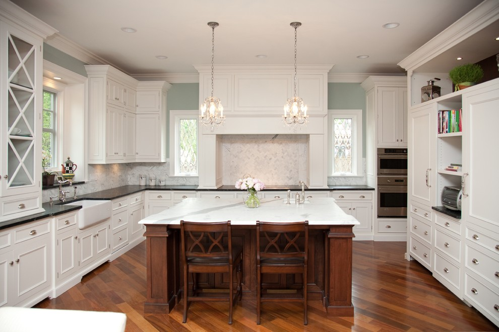 Elegant kitchen photo in Chicago with recessed-panel cabinets, a farmhouse sink, white cabinets, white backsplash and stone tile backsplash