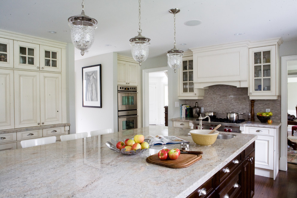 Example of a classic kitchen design in Toronto with glass-front cabinets, stainless steel appliances, white cabinets and granite countertops