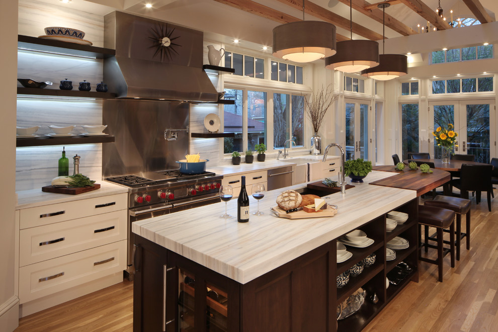 Example of a large classic medium tone wood floor eat-in kitchen design in Denver with an undermount sink, recessed-panel cabinets, white cabinets, stainless steel appliances, an island and stone slab backsplash