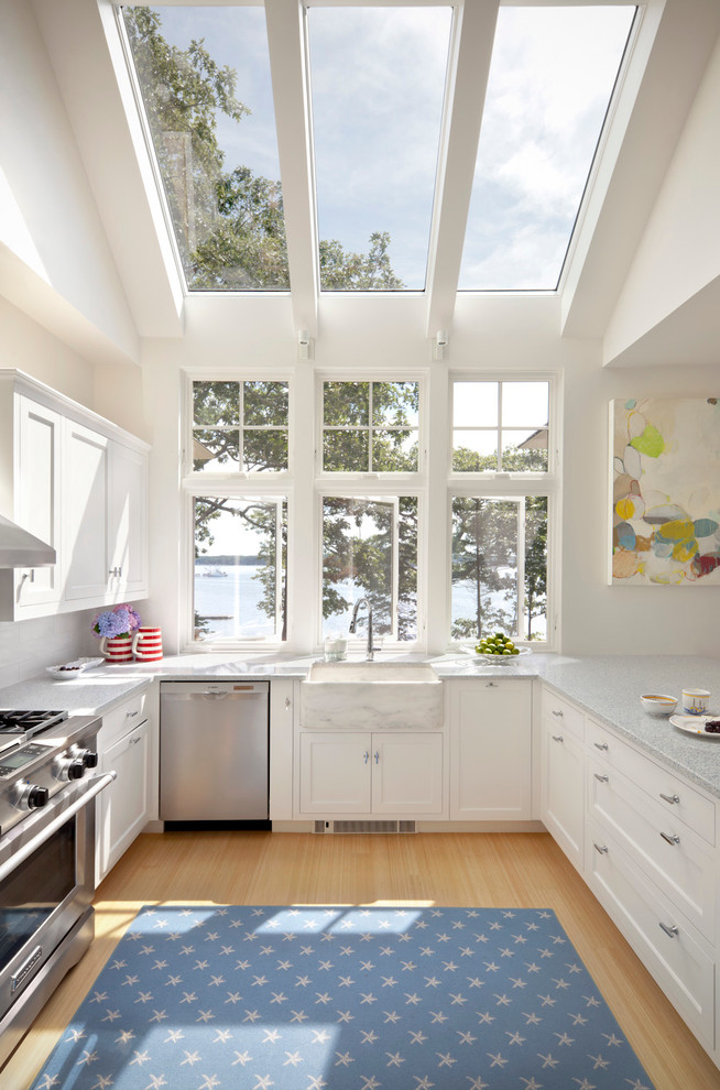 Inspiration for a coastal u-shaped light wood floor kitchen remodel in Portland Maine with a farmhouse sink, shaker cabinets, white cabinets and stainless steel appliances