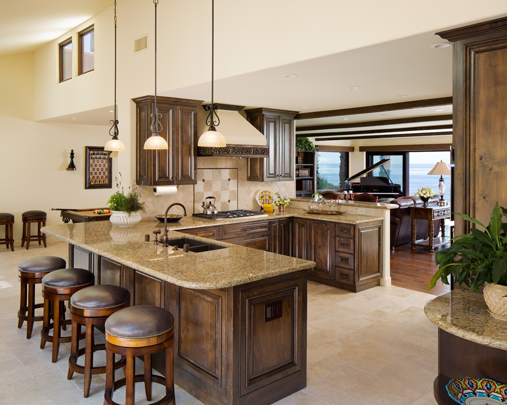 Example of a mid-sized tuscan u-shaped ceramic tile open concept kitchen design in San Diego with raised-panel cabinets, dark wood cabinets, beige backsplash, a peninsula, an undermount sink, granite countertops, porcelain backsplash and paneled appliances