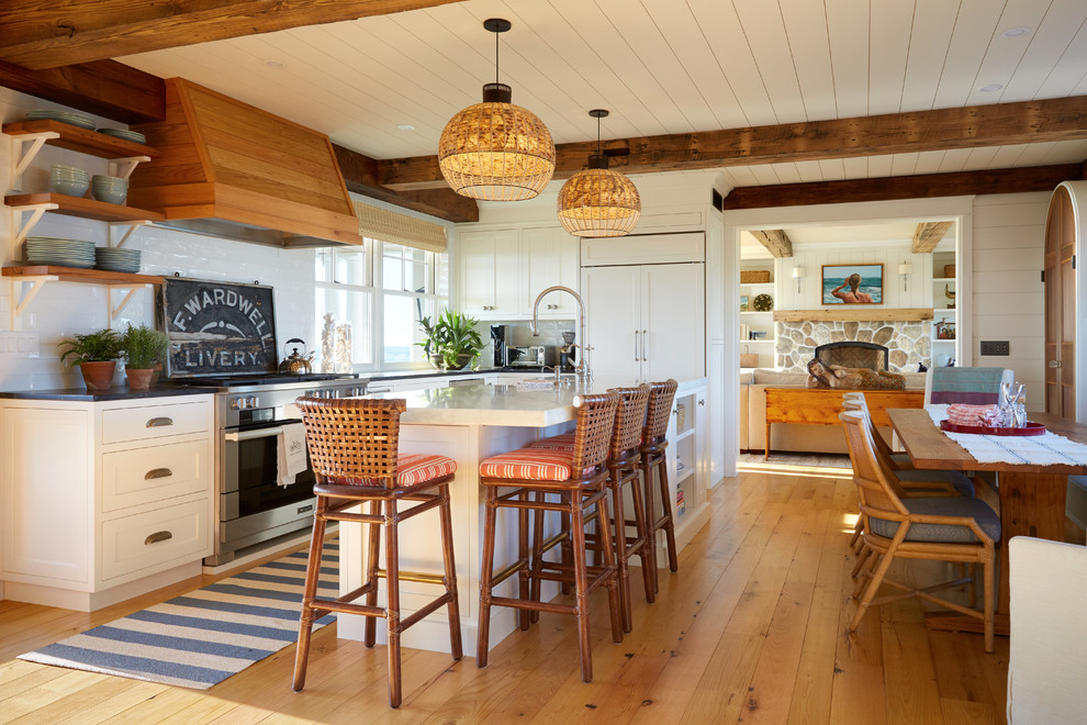 Inspiration for a coastal l-shaped light wood floor eat-in kitchen remodel in Portland Maine with shaker cabinets, white cabinets, white backsplash, paneled appliances, an island and black countertops