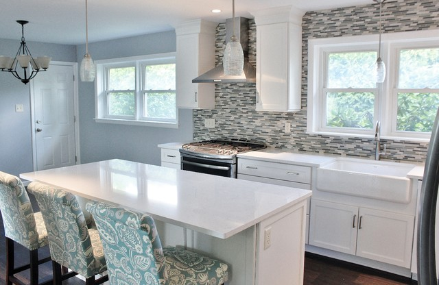 Example of a mid-sized transitional l-shaped vinyl floor and brown floor eat-in kitchen design in Philadelphia with a farmhouse sink, shaker cabinets, white cabinets, quartz countertops, blue backsplash, mosaic tile backsplash, stainless steel appliances and an island