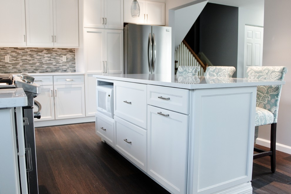 Mid-sized transitional l-shaped vinyl floor and brown floor eat-in kitchen photo in Philadelphia with a farmhouse sink, shaker cabinets, white cabinets, quartz countertops, blue backsplash, mosaic tile backsplash, stainless steel appliances and an island