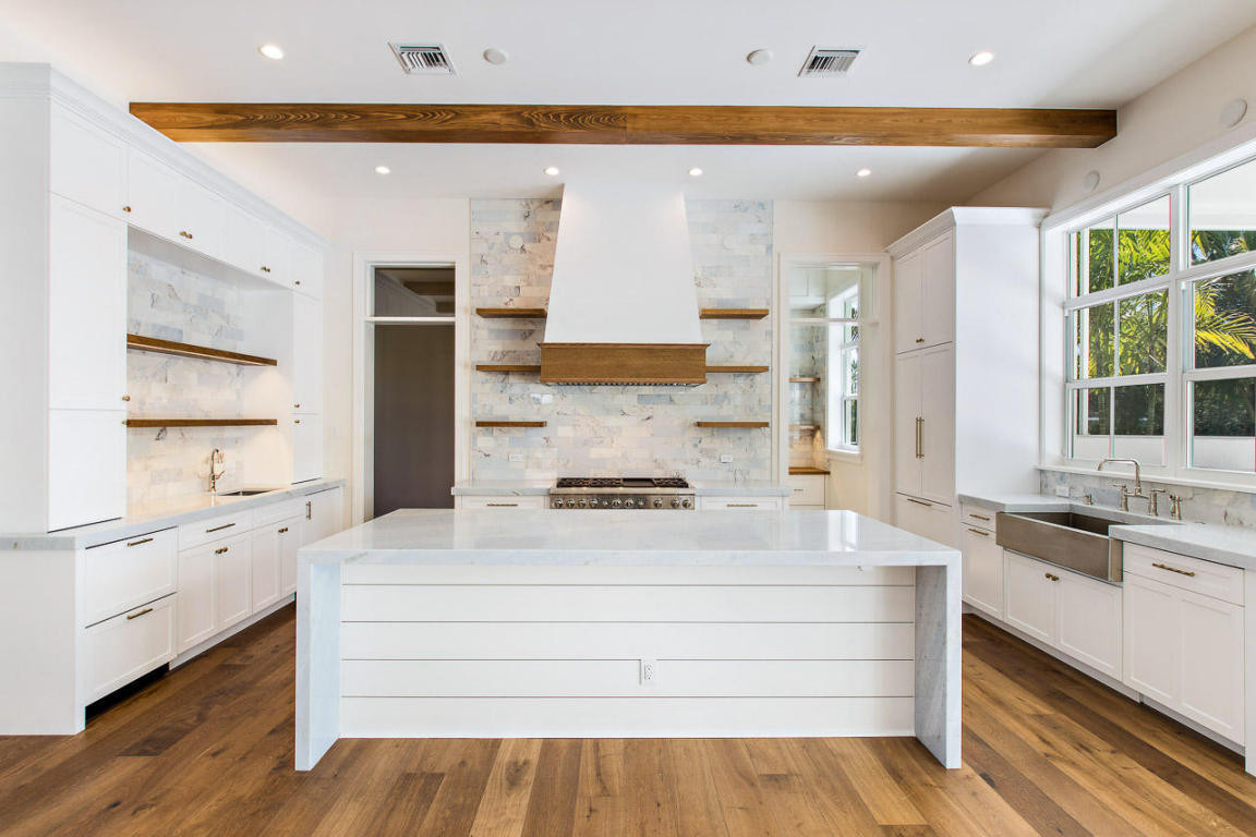 Example of a large beach style u-shaped medium tone wood floor, brown floor and exposed beam kitchen pantry design in Miami with a farmhouse sink, shaker cabinets, white cabinets, blue backsplash, mar