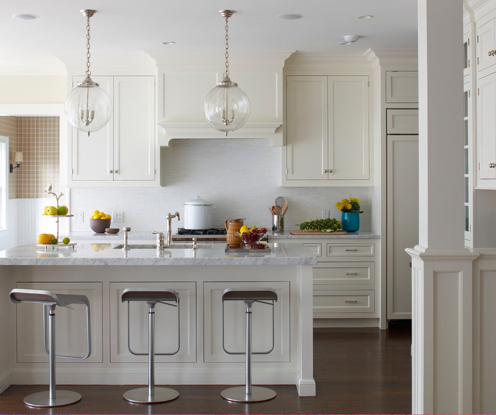 Beach style kitchen photo in New York with an undermount sink, recessed-panel cabinets, white cabinets, white backsplash and paneled appliances
