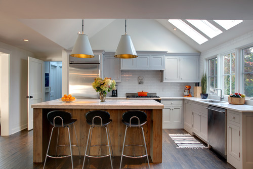 White, gray kitchen with a wooden kitchen island with 2 large scale industial pendant lights.