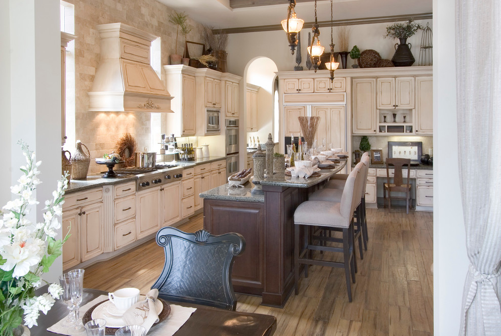 Example of a large classic single-wall medium tone wood floor and brown floor enclosed kitchen design in Miami with paneled appliances, a farmhouse sink, raised-panel cabinets, distressed cabinets, granite countertops, brown backsplash, travertine backsplash and an island