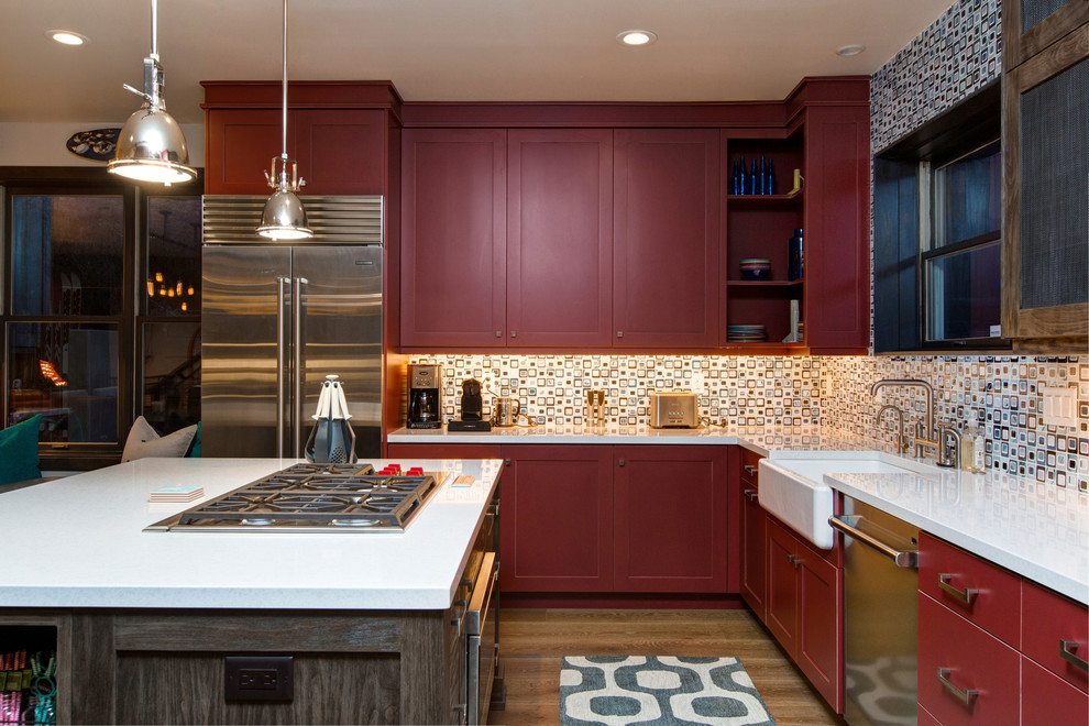 Mid-sized transitional l-shaped medium tone wood floor and brown floor kitchen photo in Salt Lake City with a farmhouse sink, quartzite countertops, stainless steel appliances, an island, shaker cabinets, red cabinets, multicolored backsplash and glass tile backsplash