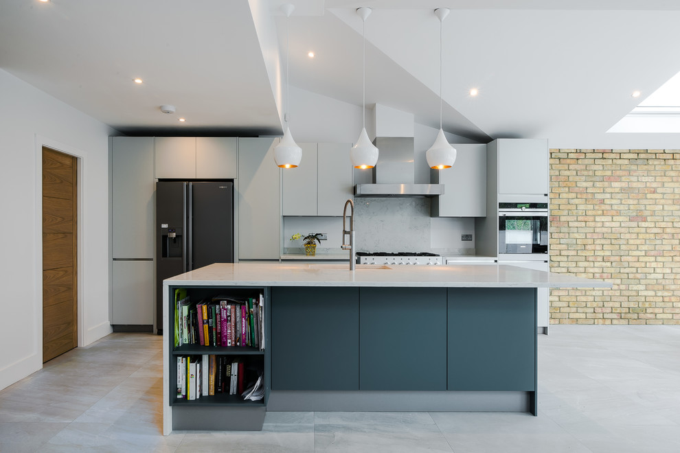 Example of a mid-sized minimalist single-wall gray floor kitchen design in London with an undermount sink, flat-panel cabinets, gray cabinets, gray backsplash, stainless steel appliances and an island