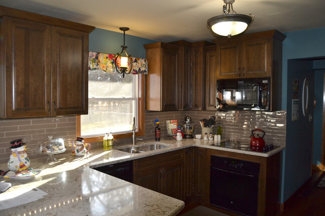 Eat-in kitchen - mid-sized transitional u-shaped medium tone wood floor eat-in kitchen idea in Other with a double-bowl sink, raised-panel cabinets, dark wood cabinets, quartz countertops, beige backsplash, glass tile backsplash, black appliances and a peninsula