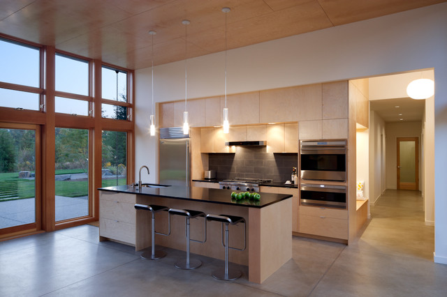 Example of a minimalist galley kitchen design in Seattle with flat-panel cabinets, light